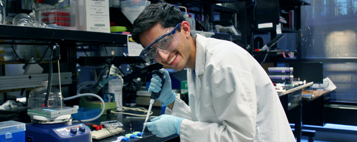 Photo of high school-aged researcher Rohan Mehrhotra in the wet lab space using a micropipette and wearing a lab coat and safety goggles.