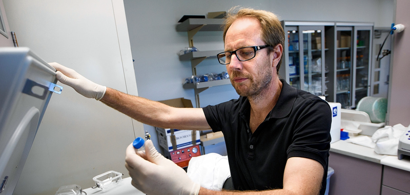 Photo of Dr. Tony Wyss-Coray examining a small test tube sample taken out from a centrifuge in the laboratory.