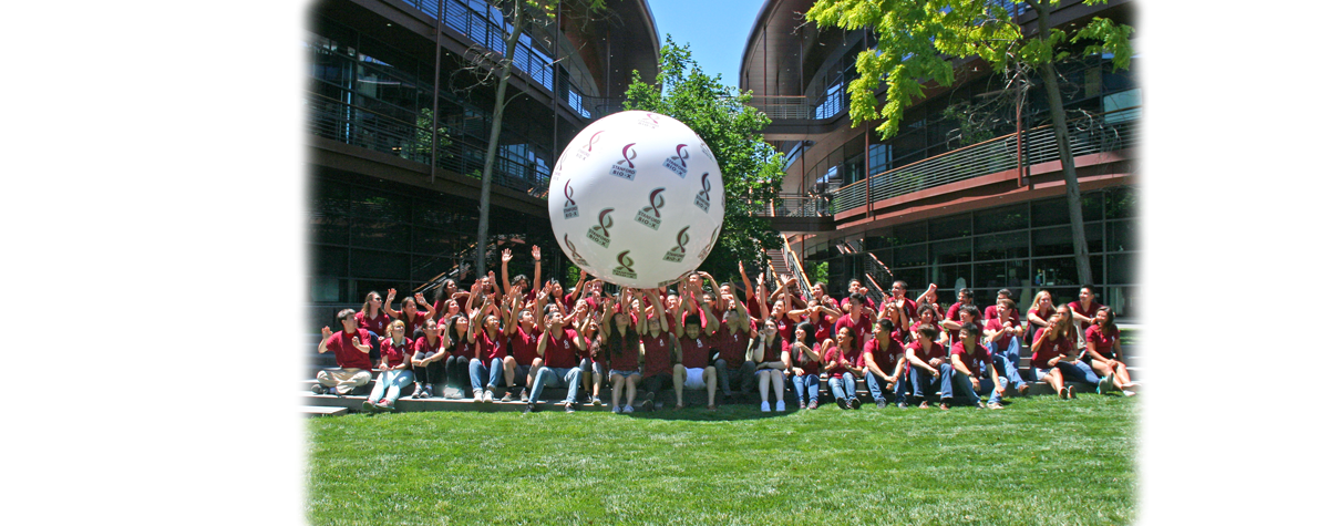 Group photo of 65 undergraduates seated, wearing red shirts and rolling a large white ball with Bio-X logos across the group's raised hands.