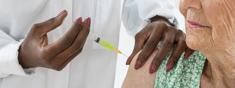Photo of an older woman receiving a vaccination injection in the shoulder.