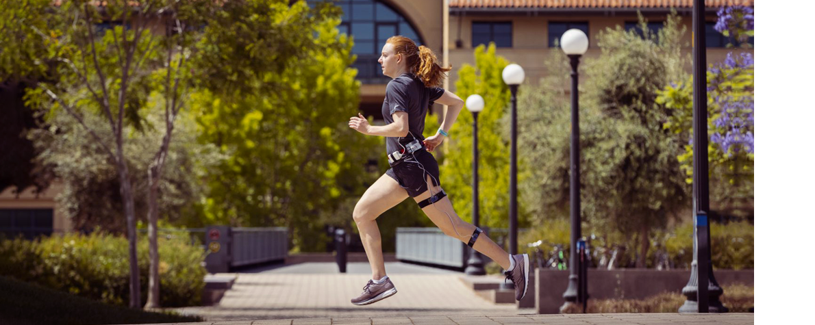 Photo of white female graduate student running across a courtyard area at Stanford, wearing running clothes and the wearable device described in the article.