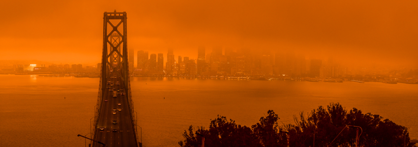 Photo of Bay Bridge in San Francisco, showing the bridge and city skyline wreathed in smoke. Whole photograph is strongly dark orange tinted due to smoke filtering the sunlight.