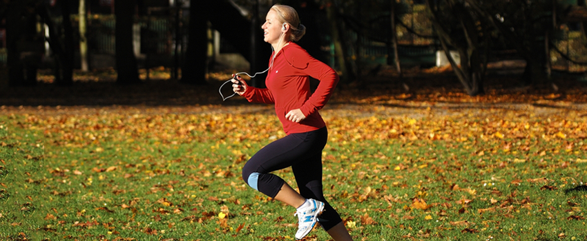 Photo of a young blonde woman running across a field with fallen leaves.